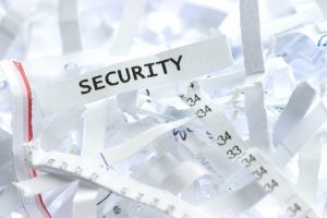 """A piece of shredded paper with a word """"security"""" written on it."""